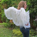 Side view of six foot outstretched white angel wings.